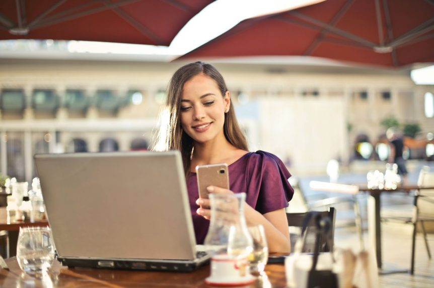 woman sat with phone and laptop